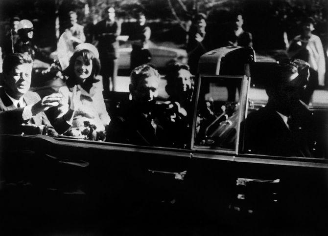 オープンカーの最後部座席に夫人と並び手を振るケネディ米大統領