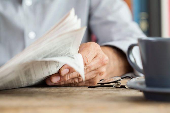 テーブルの上で新聞を読んでいる人