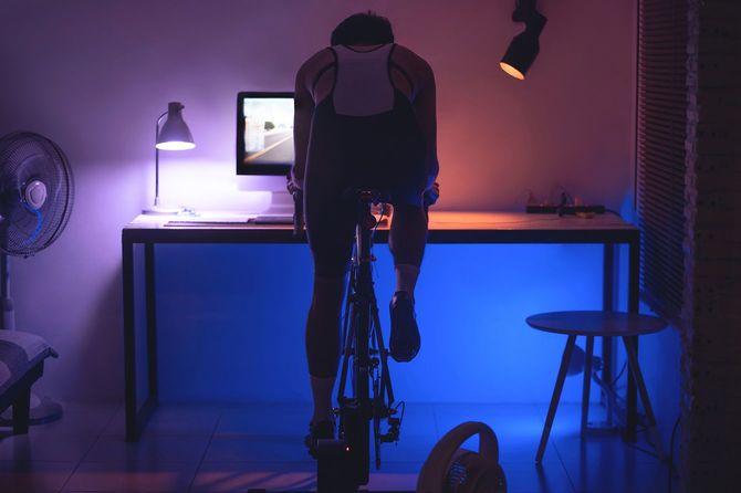 夜に自宅でマシンを使い運動している男性