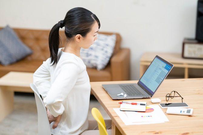 仕事中に腰の違和感を気にする女性