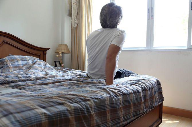 ベッドに座ったまま外を見ている男性