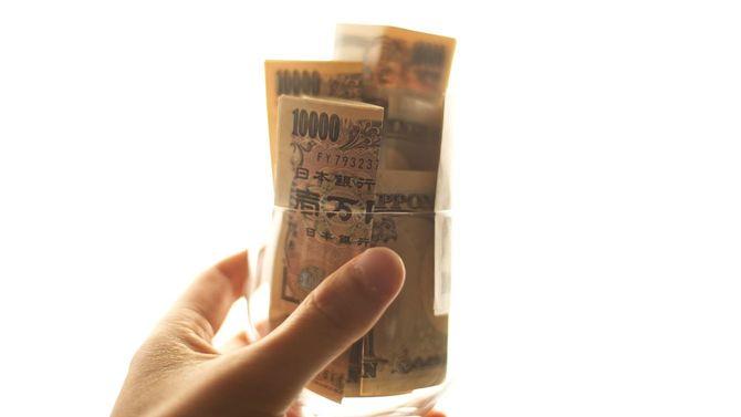 たくさんの一万円札を手に