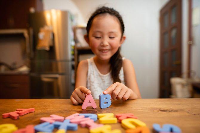 アルファベットの模型で勉強する女の子