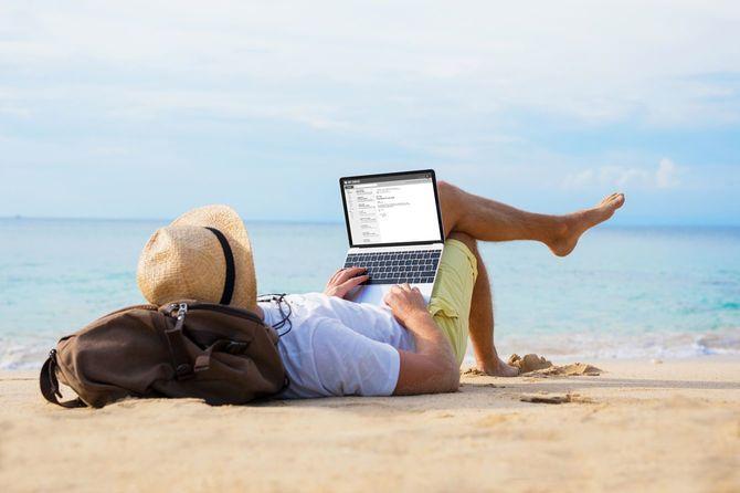 ビーチでリラックスしながらノートパソコンでメールを読んでいる人