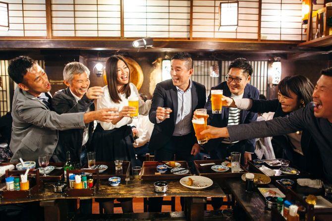 居酒屋日本居酒屋でお祝いのトーストを食べる日本人グループ