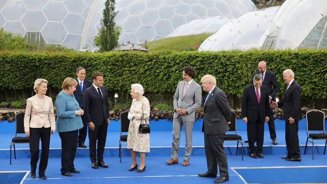 2021年6月11日、G7首脳会議の晩餐会前の写真撮影。左からメルケル首相(独)、マクロン大統領(仏)、中央のエリザベス女王を挟んでトルドー首相(加)、ジョンソン首相(英)。後方にいるのが菅義偉首相。