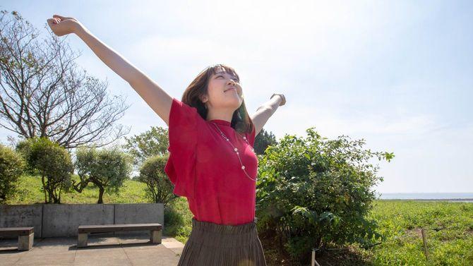 若い女性が深い太陽の下で伸びをする