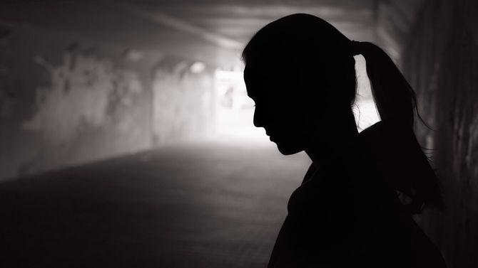 落ち込み、悲し気な女性がほの暗いトンネルの中に立っている