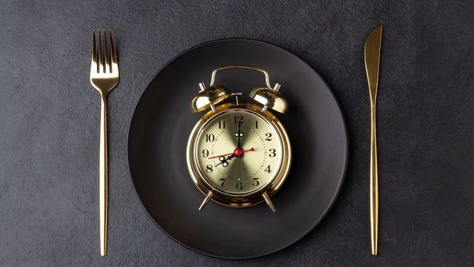金色のナイフとフォーク、黒いプレートには黄金の目覚まし時計