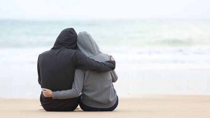 海を見ながらお互いをハグするティーンエージャーのカップル