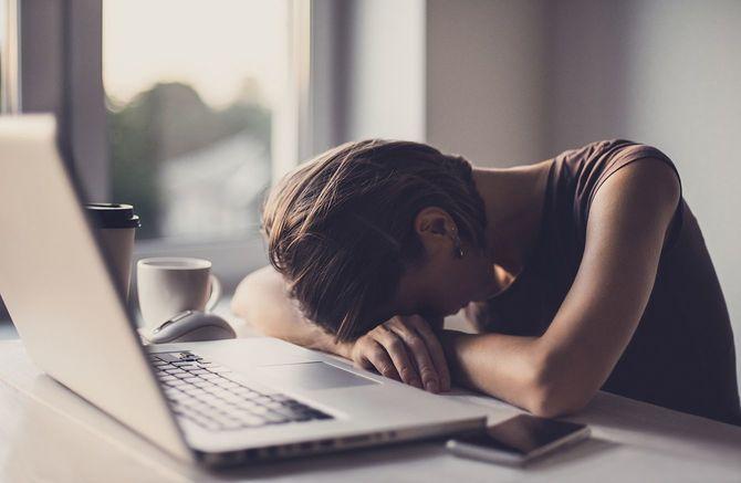 ノート パソコンとコーヒーが付いているオフィスの疲れ女性実業家