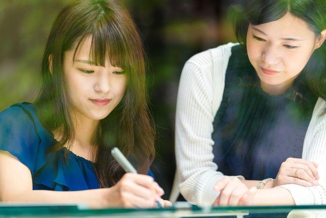 カフェで一緒に勉強する若い女性2人