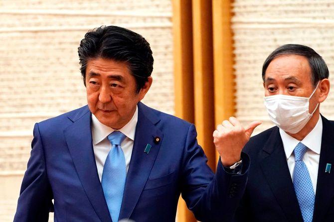菅義偉官房長官の隣でジェスチャーをする安倍晋三首相(左)=2020年5月4日、首相官邸