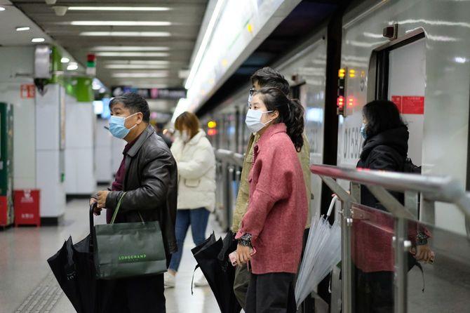 上海の地下鉄から出て行く外科用マスクを着用した人々