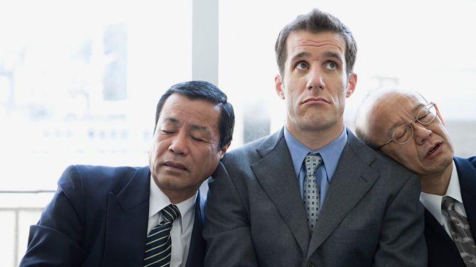 両隣のビジネスマンが、もたれかかってうたた寝している
