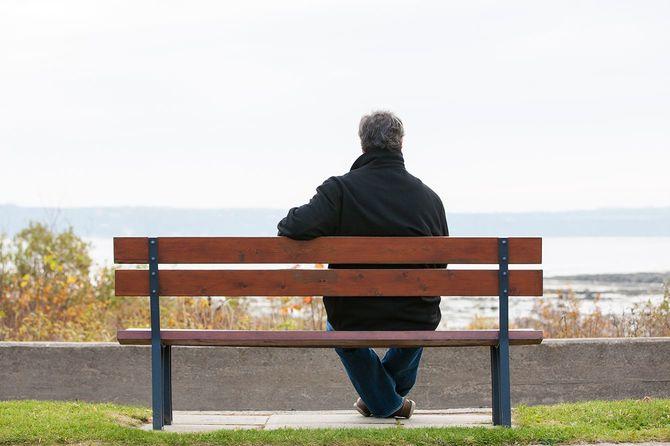 シニア男性がベンチに座り川を一望します