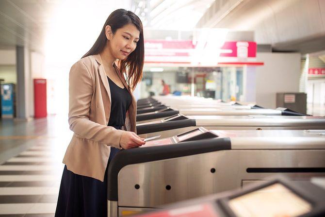 地下鉄のゲートでスマートカードで公共交通費を支払うフォーマルなビジネススーツを着ている若いアジアの女性
