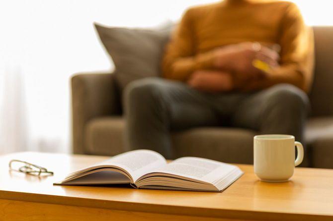 ソファに座る男性と机の上のひらいた本、マグカップ、老眼鏡