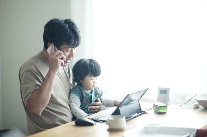 息子を膝に乗せて自宅で働く父親