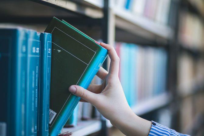 本棚から本を選ぶ女の手