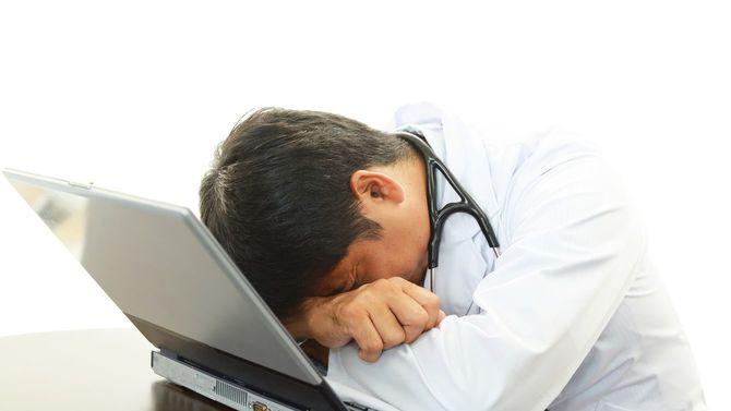 疲労した医師が机でうつぶせになっている