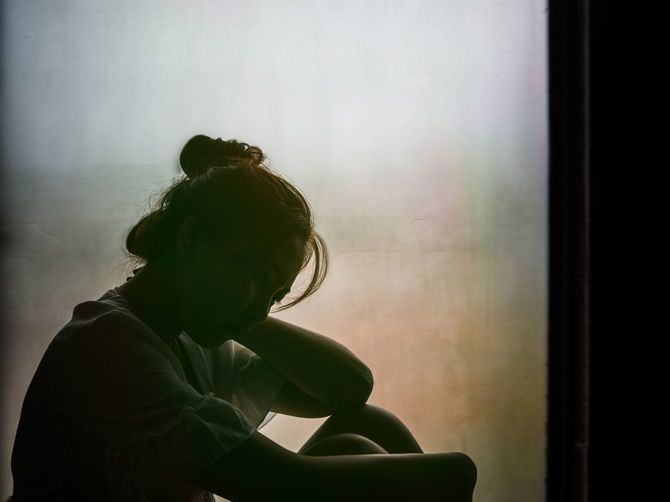 窓の前に座って意気消沈した女の子
