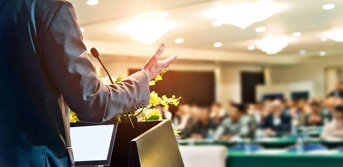 会議場で聴衆の前で演説をする認識不能なビジネスマン