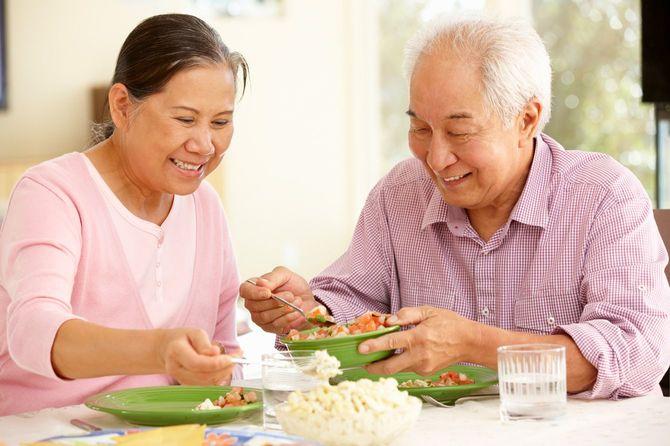 自宅で食事中のシニアカップル