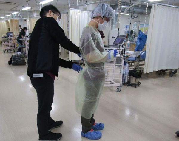 これからコロナ入院患者に接するERの医師に防護服を装着する