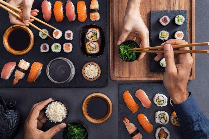 寿司を食べる人たちの手元
