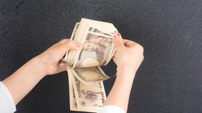 一万円札を数える女性の手元