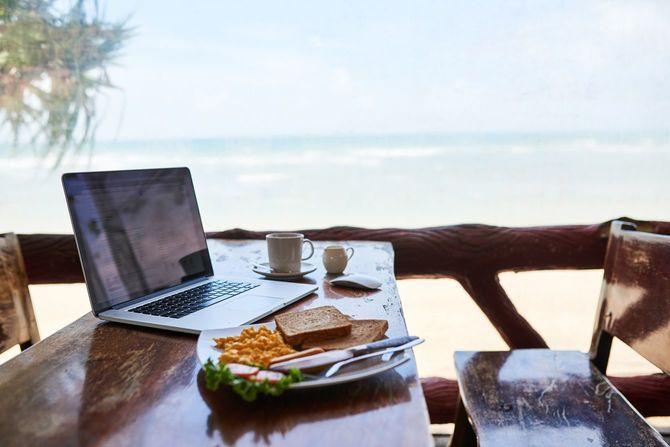 ビーチでノートパソコンを広げ、最高な朝食