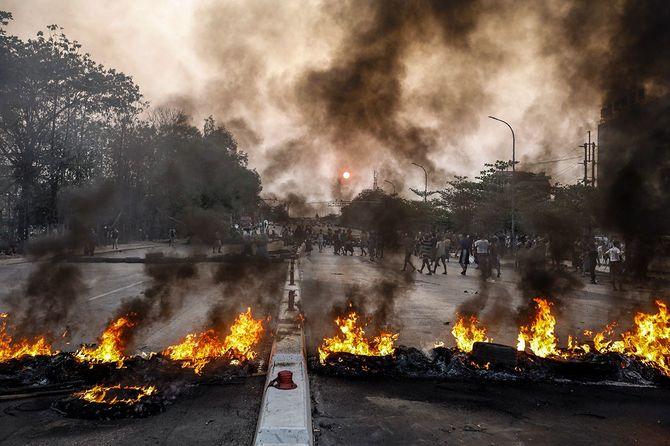 ミャンマーのヤンゴン郊外で、ブロックを燃やされたデモ参加者と住民が新しい道路ブロックを作る様子