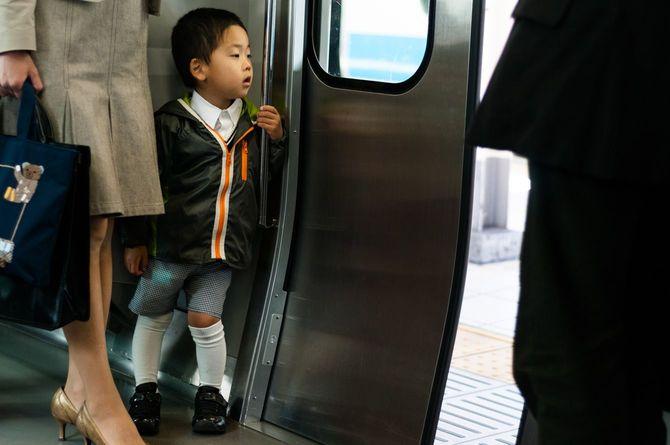 電車のドアから外を眺めている日本の子ども