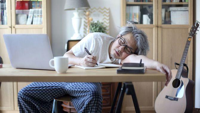 自宅での作業中、疲れて半分机にうつぶせになり目を閉じている男性