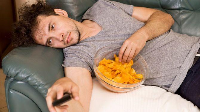 リモコンを手にした怠惰な男はソファの上で寝転がってポテトチップスを食べている