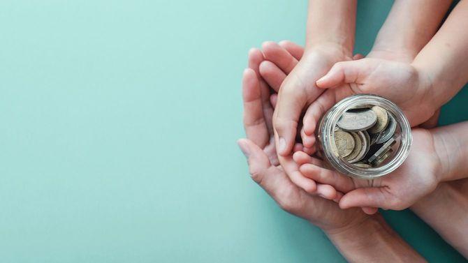 硬貨の入った瓶を持つ親子の手