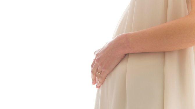 妊婦さんがお腹に手を置いて