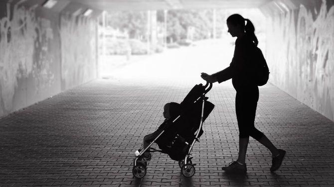 子どもの乗ったベビーカーを押して地下通路を歩く母親
