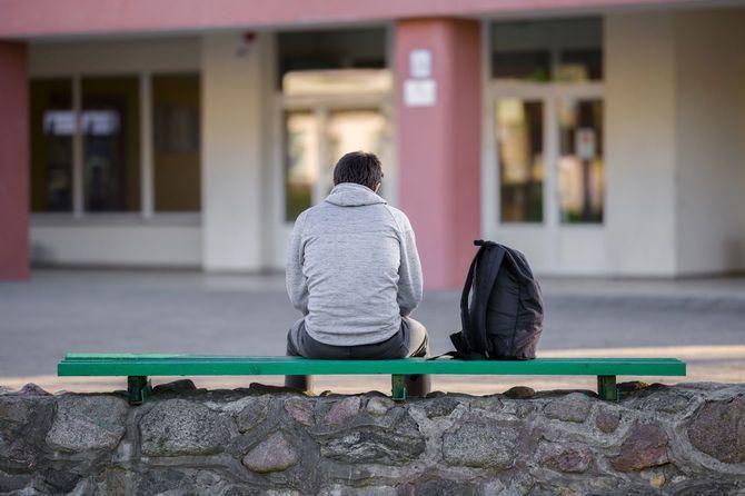 校庭のベンチに座っている一人の若い男