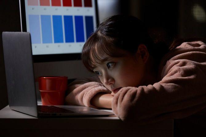 夜中に暗い自室で働く女性