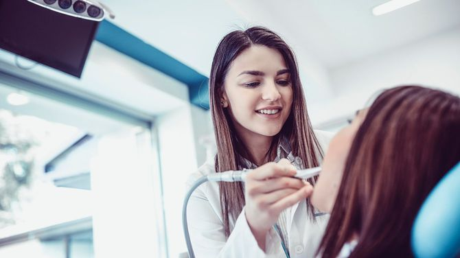 患者の歯を診察する笑顔の歯科医