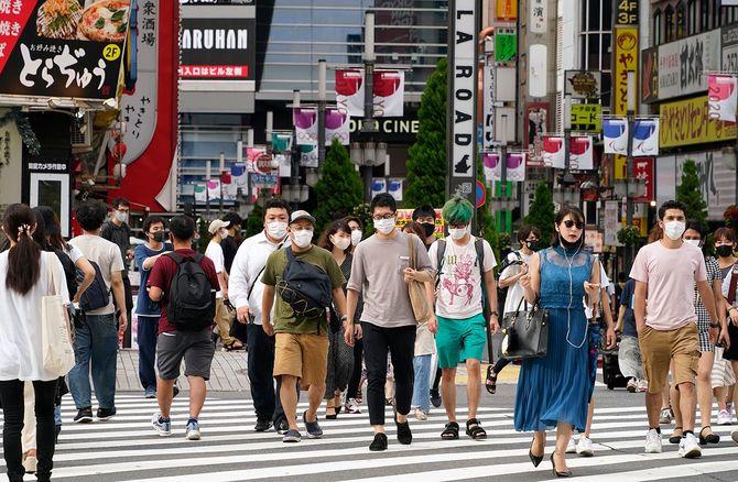 開催中の五輪の垂れ幕が掲げられた歌舞伎町を歩く人たち。東京都では7日、新たに4566人の新型コロナウイルス感染が確認され、4日連続で4000人を超えた