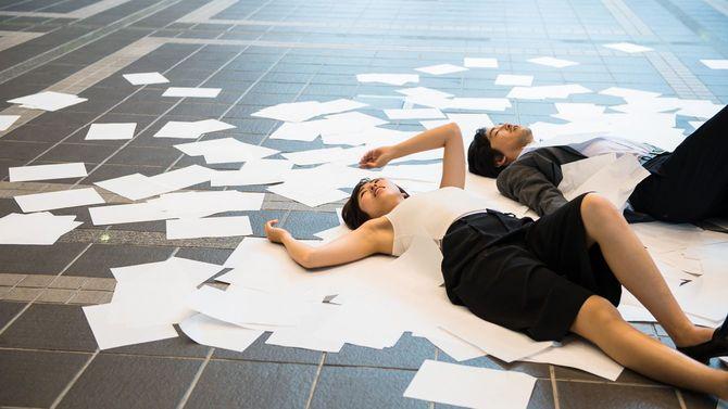 床に散らばる資料の上に疲れ果てて横たわる男女