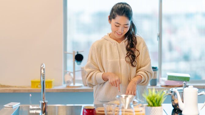 キッチンで朝食を準備する若い女性