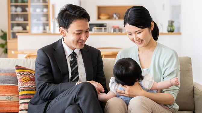 リビングで赤ちゃんにほほ笑みかける若い夫婦
