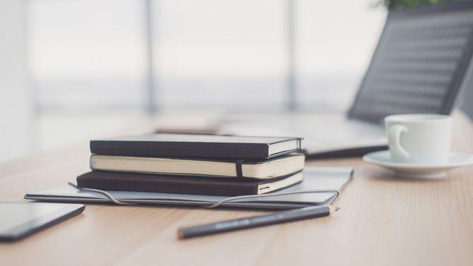 テーブルの上にペンと手帳とノートパソコン