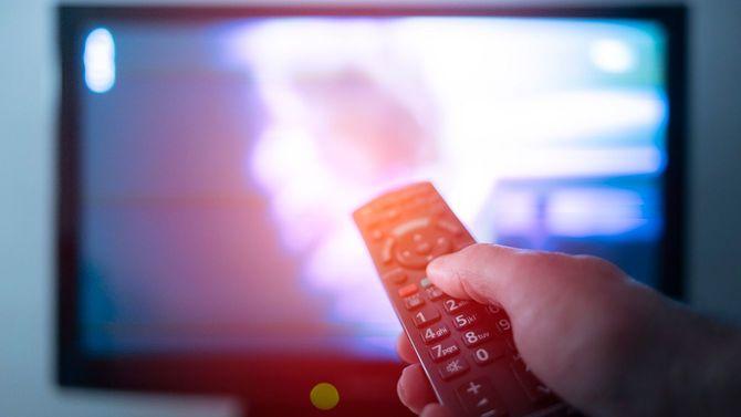 テレビの前でリモコンを持つ手元