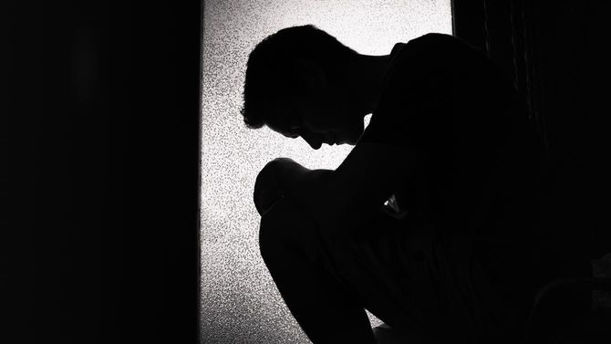 暗い部屋で一人でしゃがみ込む男性