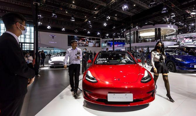 2021年4月19日、中国・上海で開催されたモーターショー「Auto Shanghai 2021」のメディア内覧日に、展示ブースに置かれた自動車「テスラモデル3」の横を通る人々。